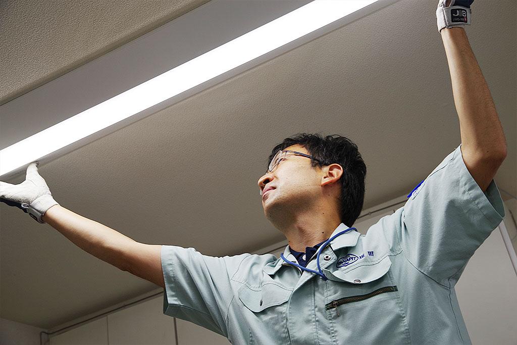 蛍光灯の交換をするスタッフ